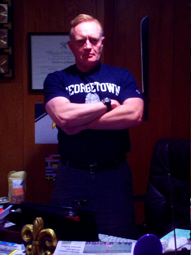 jdn-scowling-arms-crossed-office-georgetown-shirt-august-2011