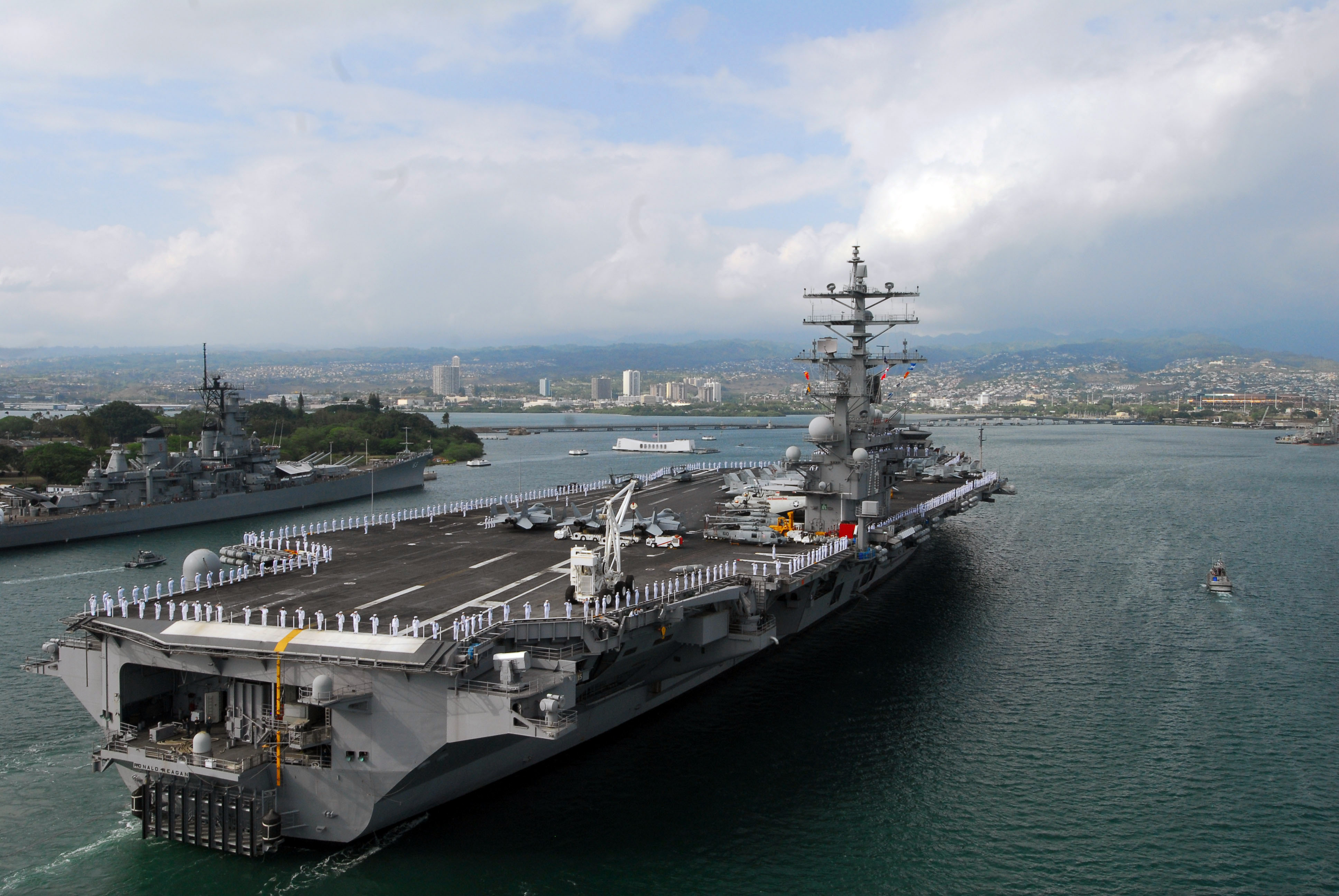 PEARL HARBOR, Hawaii (June 28, 2010) Sailors and Marines man the rails aboard the aircraft carrier USS Ronald Reagan as it passes the USS Missouri and USS Arizona memorials in Pearl Harbor.